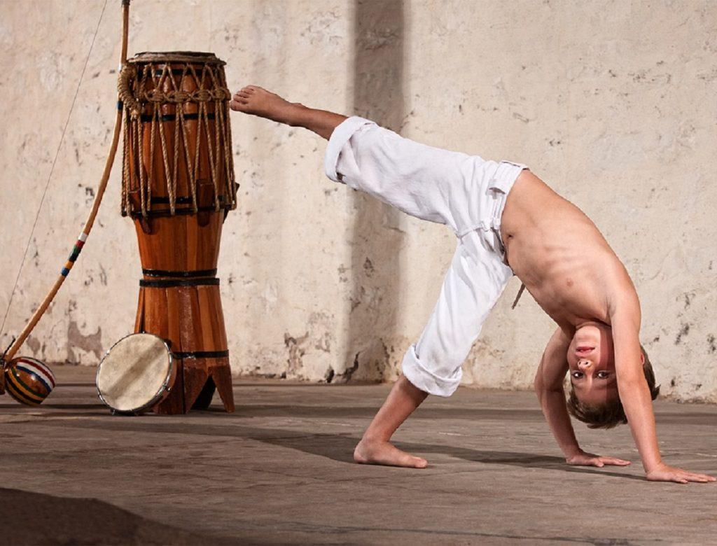 fiatal gyerek capoeira tanítvány hangszerek mellett gyakorol